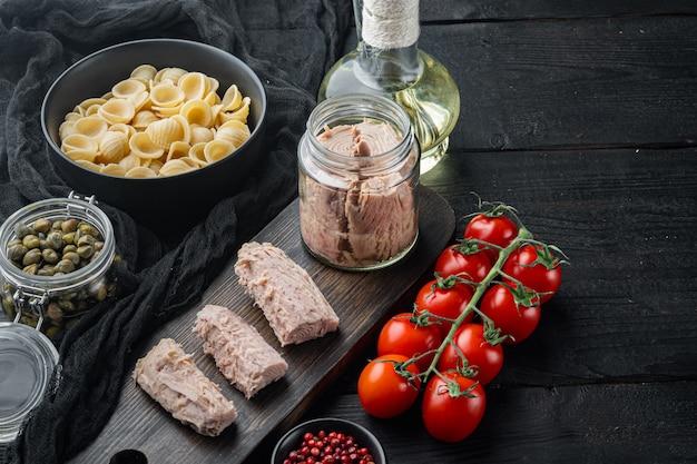 Deliciosa refeição de massa lumaconi com atum e alcaparras em mesa de madeira preta