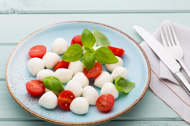 Deliciosa salada caprese com tomates cereja maduros e mini bolinhas de queijo mussarela com folhas frescas de manjericão.