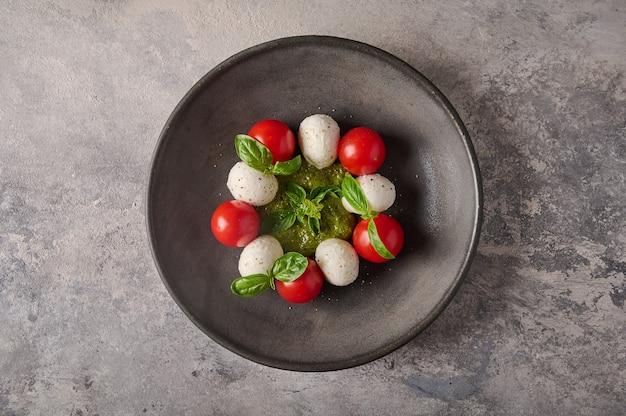 Deliciosa salada caprese italiana com tomate maduro, manjericão pesto e queijo mussarela em chapa preta