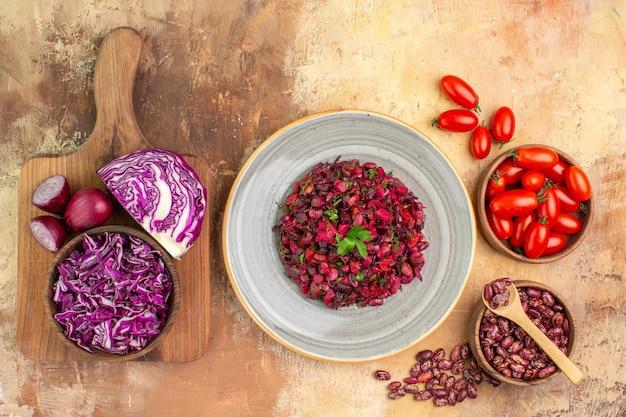 Deliciosa salada com beterraba, feijão e feijão dentro e fora do pote de tomate repolho roxo na tábua de cortar mesa de cor mista