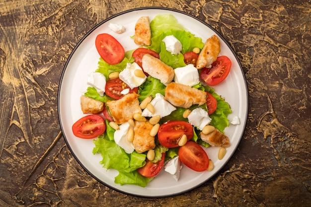 Deliciosa salada com frango quente, tomate cereja e queijo brynza macio, decorada com pinhões. tempero com azeite. tempero com azeite. vista do topo