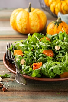 Deliciosa salada com rúcula assada de abóbora avelã e sementes de gergelim em prato marrom dieta paleo