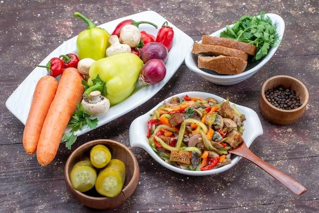 Deliciosa salada de carne com carne fatiada e vegetais cozidos junto com picles, pão e verduras na mesa marrom, prato de refeição de carne