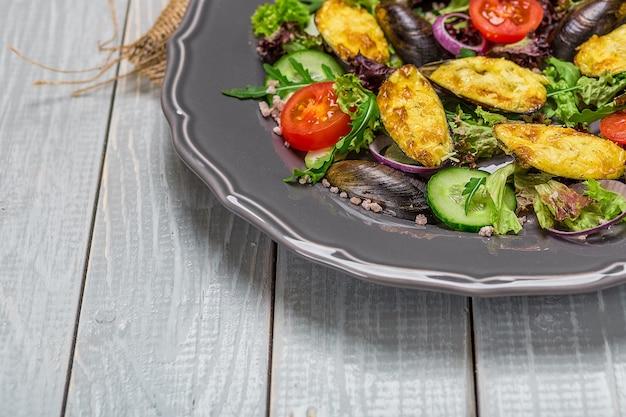 Deliciosa salada de frutos do mar com legumes e mexilhões na mesa de madeira em estilo rústico. a apresentação original do prato do chef