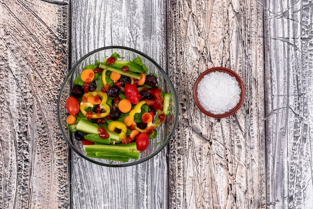 Deliciosa salada de legumes com pepino, tomate, pimenta e azeitona e tigela de sal
