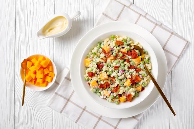 Deliciosa salada de macarrão com ervilhas, bacon crocante frito, queijo cheddar em cubos e cebola roxa em uma tigela branca com uma colher de ouro, molho de maionese na mesa, vista horizontal, flatlay