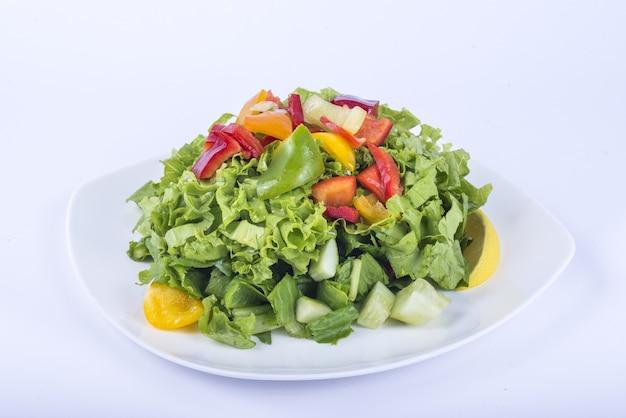 Deliciosa salada de vegetais com folhas em um prato branco com fatias de pimentão por cima