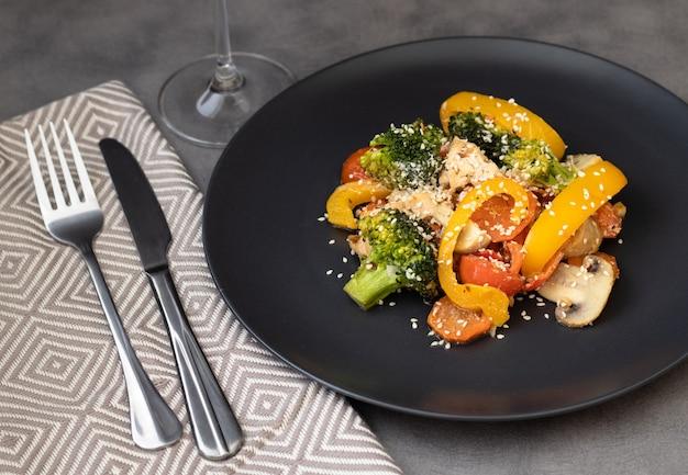 Deliciosa salada feita de brócolis, tomate cereja, cogumelos pimenta amarela e pedaços de peito de frango decorado com sementes de gergelim