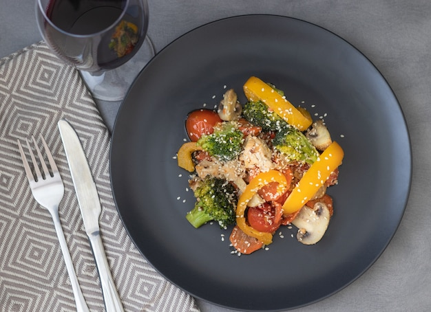 Deliciosa salada feita de brócolis, tomate cereja, pimenta amarela, cogumelos, pedaços de peito de frango e sementes de gergelim com um copo de vinho