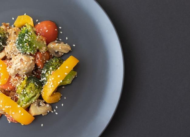 Deliciosa salada feita de brócolis, tomate cereja, pimenta amarela, cogumelos, pedaços de peito de frango e sementes de gergelim