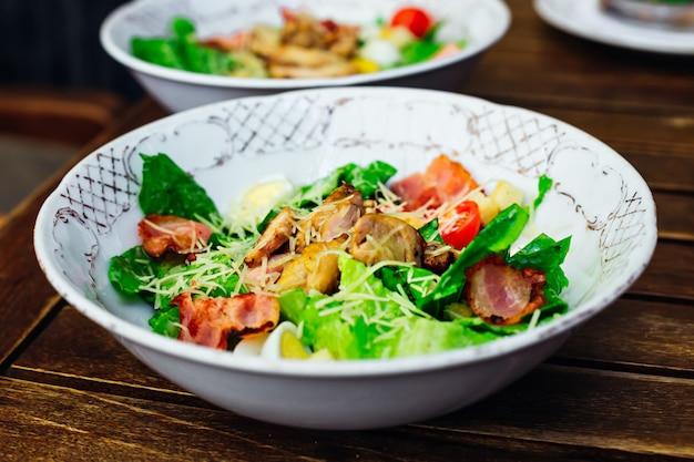 Deliciosa salada fresca com legumes e bacon em uma mesa de madeira