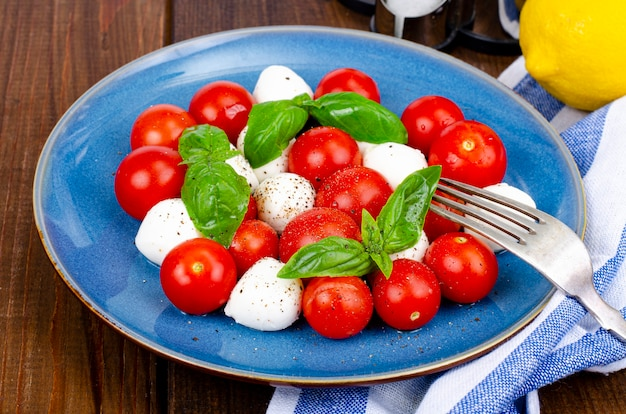 Deliciosa salada italiana caprese com manjericão, mussarela e tomate cereja. foto do estúdio.