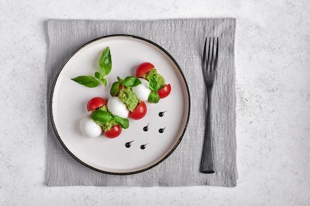 Deliciosa salada italiana caprese com tomates maduros, manjericão fresco e queijo mussarela com garfo no guardanapo de linho