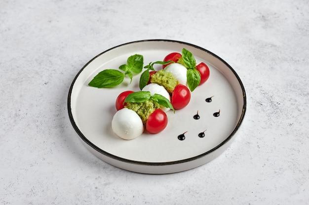 Deliciosa salada italiana caprese com tomates maduros, manjericão fresco e queijo mussarela