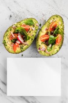 Deliciosa salada saudável em uma composição de abacate com um cartão branco.