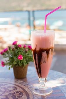 Deliciosa sobremesa de leite com chocolate e amora silvestre na mesa de cerâmica e fundo desfocado