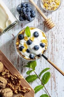 Deliciosa sobremesa de mirtilos, iogurte e cereais (muesli). café da manhã refrescante e saudável com iogurte, mirtilo, frutas secas e frutas secas. vista do topo.