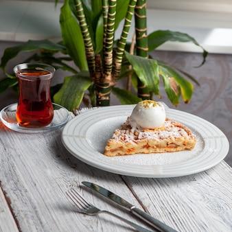 Deliciosa sobremesa em um prato com chá, vista de alto ângulo de plantas em um fundo branco de madeira