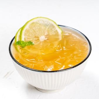 Deliciosa sobremesa gelada aiyu geléia de gelo em uma tigela branca com cobertura de limão verde e hortelã