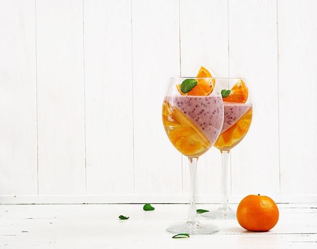 Deliciosa sobremesa panna cotta com coulis de framboesa e geléia de tangerina com champanhe em copos