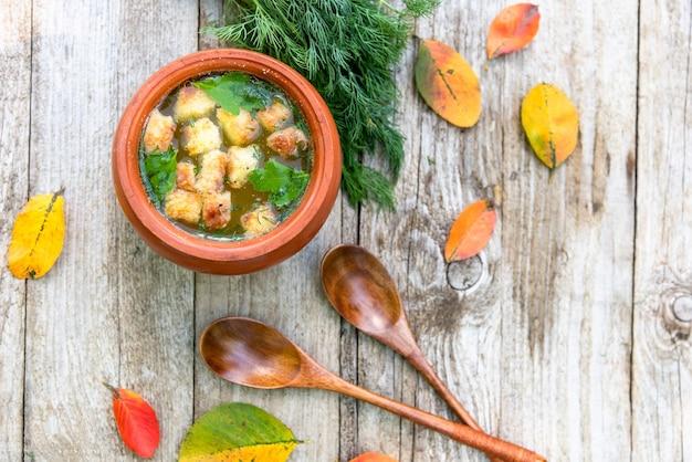 Deliciosa sopa com croutons em uma panela de barro.
