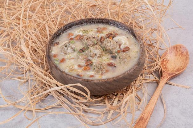 Deliciosa sopa de cogumelos em uma tigela de madeira com uma colher.