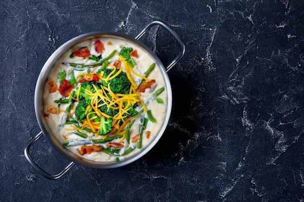 Deliciosa sopa de creme com brócolis, feijão verde, bacon frito e queijo cheddar ralado em uma caçarola de metal