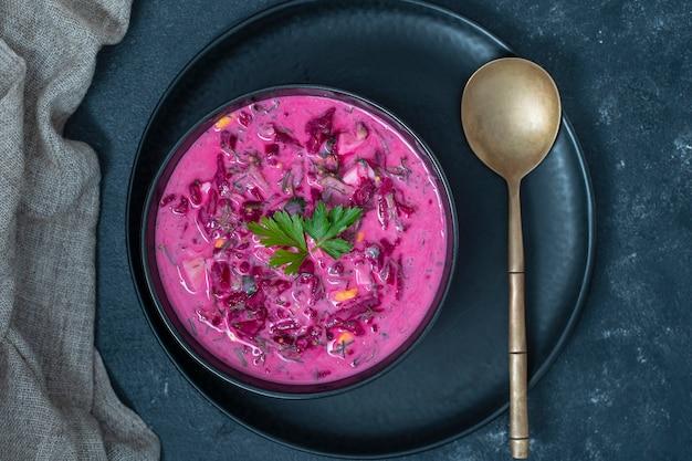 Deliciosa sopa fria de beterraba com pepino, ovo cozido e rabanete em uma tigela preta na mesa