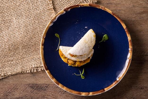 Deliciosa tapioca, um petisco brasileiro feito com farinha de mandioca e camarão, mandioca no prato azul