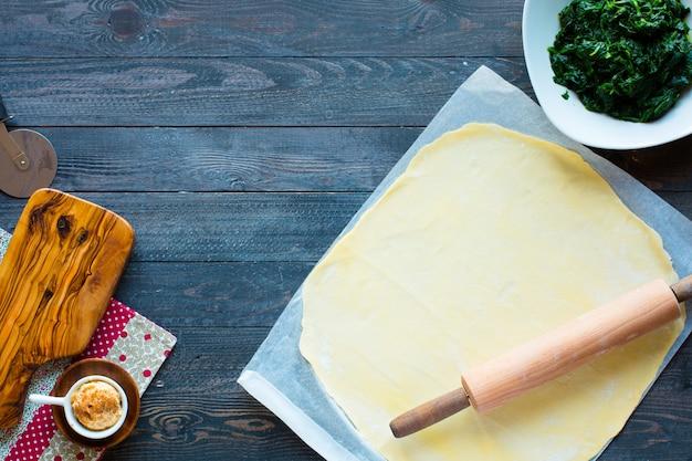 Deliciosa torta com espinafre, feita em casa, sobre um fundo de madeira