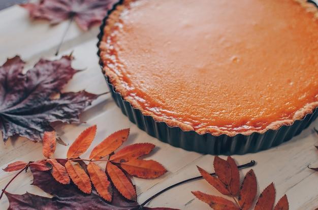 Deliciosa torta de abóbora caseira fresca em fundo branco de madeira com folhagem de outono