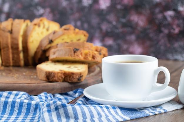 Deliciosa torta em uma travessa de madeira com uma xícara de café à parte