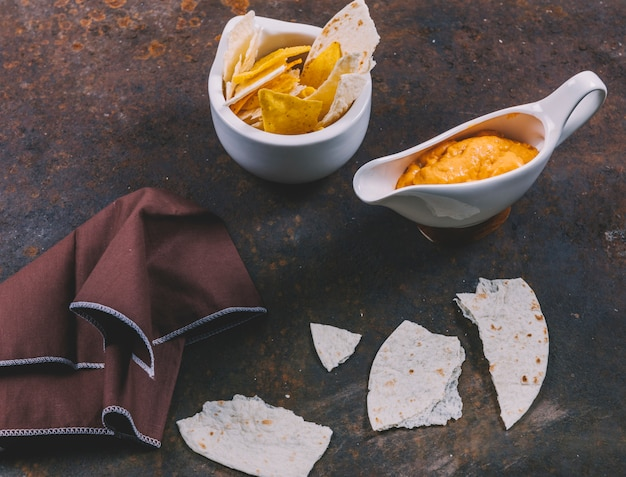 Deliciosa tortilla mexicana com nachos em tigela com molho de queijo e guardanapo sobre fundo enferrujado