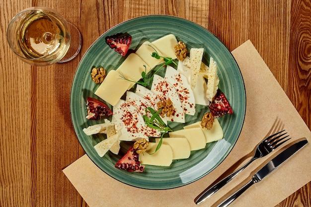 Deliciosa travessa com três variedades de queijos georgianos fatiados tradicionalmente temperados com óleo picante com pimenta malagueta servida com romã, nozes e copo de vinho branco na mesa de madeira