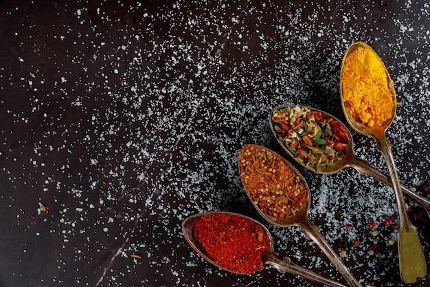 Deliciosa variedade de ingredientes de especiarias à terra no fundo escuro de madeira