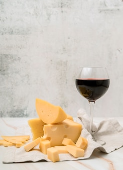 Deliciosa variedade de queijo com copo de vinho tinto