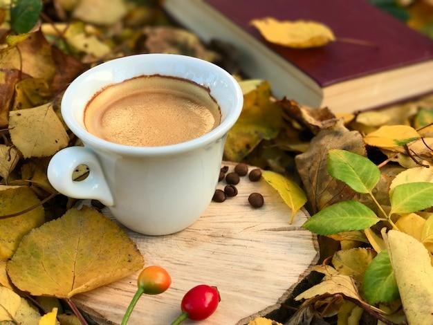 Deliciosa xícara de café em um toco de madeira entre folhas amarelas caídas