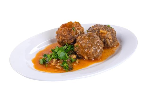 Deliciosas almôndegas suecas com molho marrom farto com salsa no prato branco