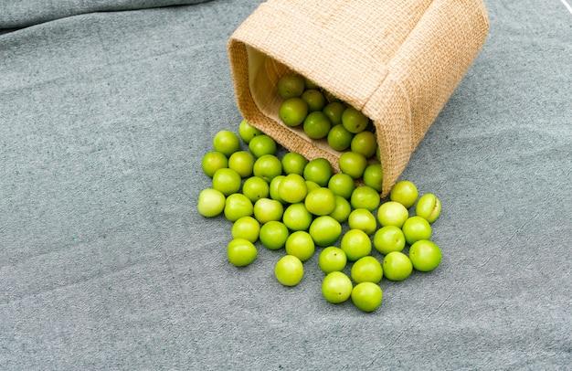 Deliciosas ameixas verdes em um pequeno saco de estopa vista de alto ângulo em pano de piquenique cinza
