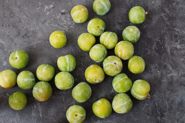 Deliciosas ameixas verdes maduras greengages fundo de concreto texturizado preto