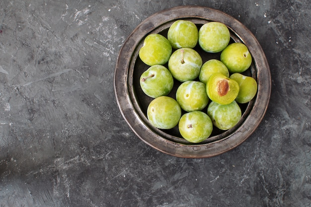 Deliciosas ameixas verdes maduras greengages na placa preta de cerâmica