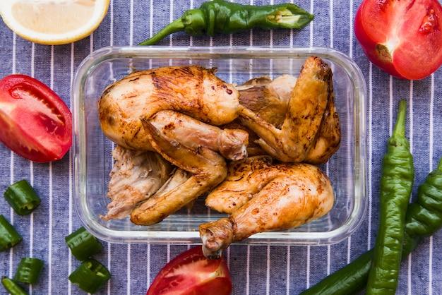 Deliciosas asas de frango assadas, servidas com tomates e pimentões verdes
