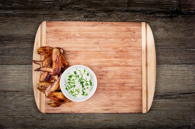 Deliciosas asas de frango grelhado com molho de alho em uma placa de corte em madeira rústica com vista superior copyspace