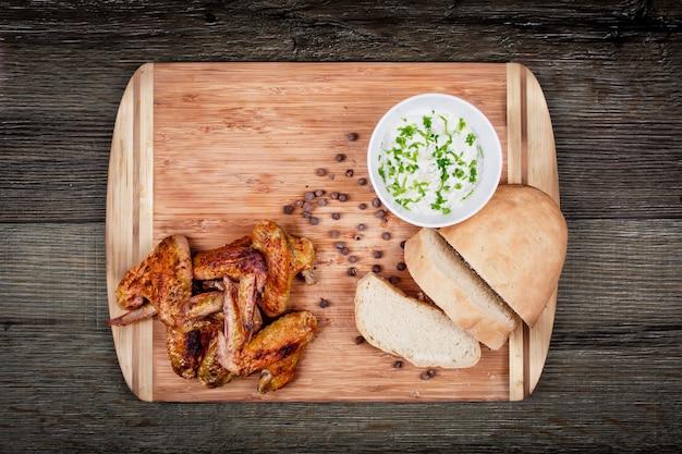 Deliciosas asas de frango grelhado com molho de alho, especiarias, temperos e pão sobre uma tábua na vista superior rústica de madeira