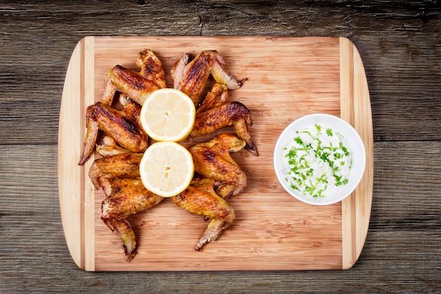 Deliciosas asas de frango grelhado com molho de alho, limão sobre uma tábua na vista superior rústica de madeira