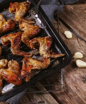 Deliciosas asas de frango na mesa de madeira