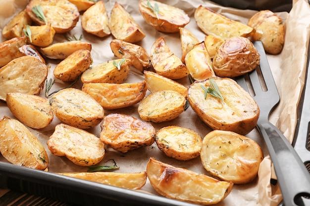 Deliciosas batatas assadas com alecrim na assadeira, closeup