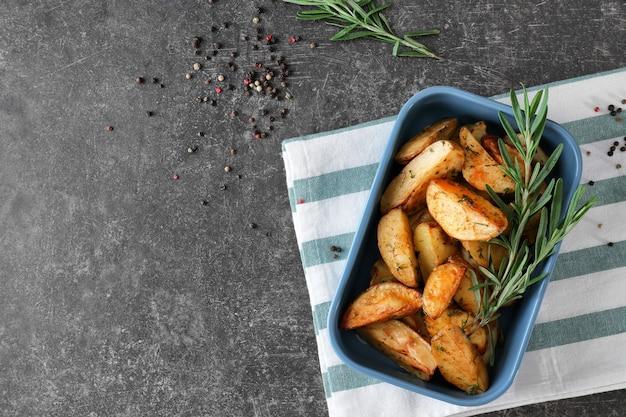 Deliciosas batatas assadas com alecrim na assadeira na mesa
