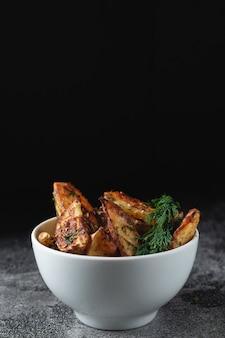 Deliciosas batatas assadas do campo com endro e especiarias em uma tigela branca sobre uma mesa de pedra escura