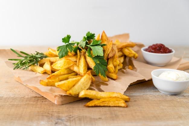 Deliciosas batatas fritas com maionese na mesa de madeira